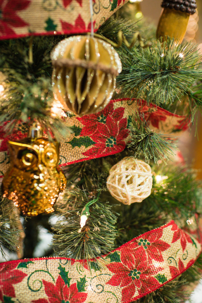 Close up image of a decorated Christmas tree. The tree is green pine and is decorated with gold acorns and owls and a ribbon that is burlap with a poinsettia pattern.