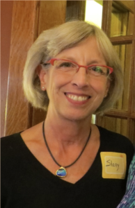 Smiling blonde woman wearing glasses and black top and a bluestone necklace.