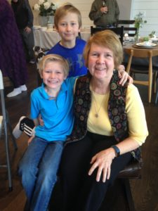 Group photo. From left to right:in front young boy seated wearing blue shirt and jeans. He is blonde haired and smiling. A sandy brown haired boy is standing behind him also smiling, also wearing blue shirt. Gail Tate is seated next to the boy to the right. She is wearing a yellow shirt, black vest, black pants. She has sandy brown hair and is smiling.